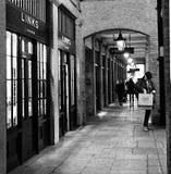 Ett svartvitt skott av manliga sammanlänkningar för en shoppareyttersida av den London Covent trädgården, London UK i November 20 royaltyfri bild