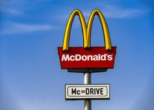 Ett tecken för McDonald ` s McDrive mot den blåa himlen Arkivbilder