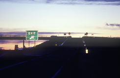 Ett tecken för motorvägutgång på skymning Arkivfoton