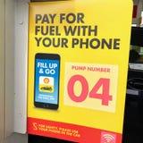 Ett tecken 'lön för bränsle med din telefon ', royaltyfri bild