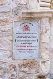 Ett tecken med inskriften - den syrianska ortodoxa kyrkan - itu språk - som är arabiska, och engelska nära ingången till den kyrk arkivfoto