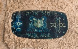 Ett tecken med namnet av gatan i hebré - gränd av tecknet av zodiakLejonet in på den gamla staden Yafo i telefon Aviv-Yafo i Isra Arkivfoto
