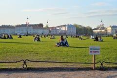 Ett tecken på gräsmattan att inte gå och folket på gräsmattan på set Arkivfoto