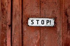 Ett tecken som säger `` stoppet `` på den gamla dörren Arkivfoto