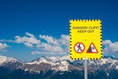 Ett tecken som varnar om faran av att falla in i avgrunden mot bakgrunden av höga snö-täckte bergmaxima Arkivbilder