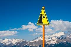 Ett tecken som varnar om faran av att falla in i avgrunden mot bakgrunden av höga snö-täckte bergmaxima Royaltyfri Fotografi