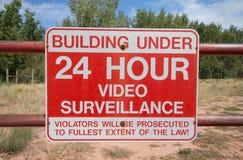 Ett tecken varnar inkräktare av video bevakning Arkivfoto