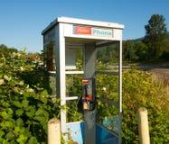 Ett telefonbås som täckas med lövverk på en bensinstation i Kanada arkivfoton