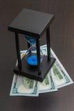 Ett timglas med dollar Royaltyfri Fotografi