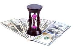 Ett timglas står på dollar arkivfoton