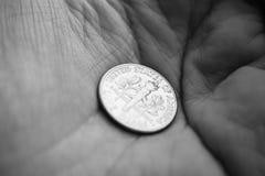 Ett tiocentaremynt på en gömma i handflatan av en hand Arkivbild