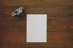 Ett tomt ark och en tappningkamera på en mörk trätabell Arkivbild