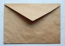 ett tomt guld- kuvert på tabellen, kraft papper, kopieringsutrymme royaltyfri bild