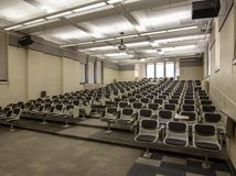 Ett tomt högskolaklassrum med rader av platser royaltyfri fotografi