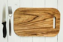 Ett tomt kökbräde med en kniv och gaffel på en vit trätabell Töm utrymme arkivbild