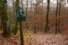 Ett tomt varningstecken längs en skogslinga Fotografering för Bildbyråer