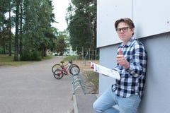 Ett tonåringpojkeskolbarn eller student sitter på trappan och att läsa en bok, bärande exponeringsglas, i en skjorta som ler, en  royaltyfria bilder