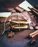 Ett torn av chokladstänger som slås in som en chokladgåva Olika chokladstycken, kryddor, kakaopulver och muttrar över mörkt trä Royaltyfri Fotografi