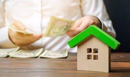 Ett tr?hus och en man som r?knar pengar verkligt begreppsgods Sale och k?p av hus Inteckna ?verenskommelse Betalning av skulden fotografering för bildbyråer
