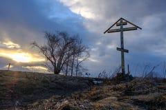 Ett träkors på solnedgången Arkivfoto