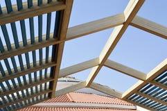 Ett trätak är modernt från solen med bräden med strålar och hål på bakgrunden av ett belagt med tegel tak med röda tegelplattor royaltyfria foton