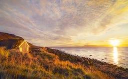 Ett traditionellt gammalt hus med ett tak som ?r bevuxet med gr?s och ett t?lt p? stranden iceland arkivfoton