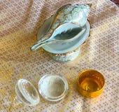 Ett trumpetsnäckaskal och glod bowlar, pudrar i bunke arkivfoton