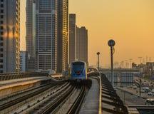 Ett tunnelbanadrev som kör på spår på solnedgången arkivfoton