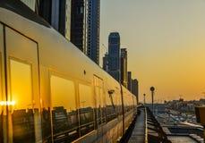 Ett tunnelbanadrev som kör på spår på solnedgången royaltyfri bild