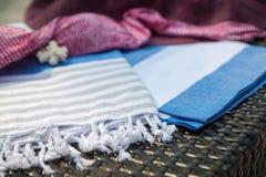 Ett turkiskt peshtemal för vit, för blått och för beiga/handduk, rosa bikiniöverkant, sugrörhatt och vitsnäckskal på rottingdagdr Arkivbild