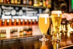 Ett två exponeringsglas av ljust öl på en bar med bokehbakgrund royaltyfri foto