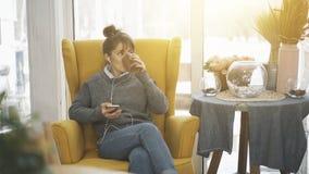Ett ung flickasammanträde i en stor stol med en telefon som lyssnar till musik som dricker te arkivfoton