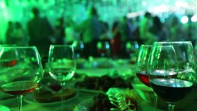 Ett ungdomparti i en restaurang eller en nattklubb, banketttabeller med alkohol och mat mot bakgrunden av konturer arkivfilmer