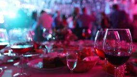 Ett ungdomparti i en restaurang eller en nattklubb, banketttabeller med alkohol och mat mot bakgrunden av konturer stock video