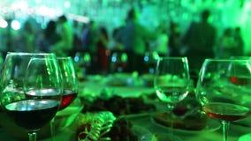 Ett ungdomparti i en restaurang eller en nattklubb, banketttabeller med alkohol och mat mot bakgrunden av konturer lager videofilmer
