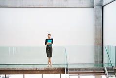 Ett ungt affärskvinnaanseende av trappa i regeringsställning som bygger royaltyfria foton