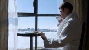 Ett ungt attraktivt mansammanträde på en tabell av fönstret som dricker te, kaffe och skriver ett SMS meddelande på en mobil arkivbilder