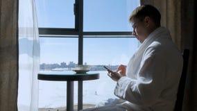 Ett ungt attraktivt mansammanträde på en tabell av fönstret som dricker te, kaffe och skriver ett SMS meddelande på en mobil royaltyfri fotografi