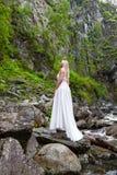 Ett ungt blont flickaanseende med hennes baksida i en vit budoarklänning i bergen mot en bakgrund av en vattenfall och arkivfoto