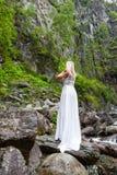 Ett ungt blont flickaanseende med hennes baksida i en vit budoarklänning i bergen mot en bakgrund av en vattenfall och royaltyfri foto