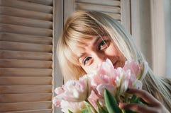 Ett ungt blont kvinnainnehav blommar av fönstret som ler arkivfoto