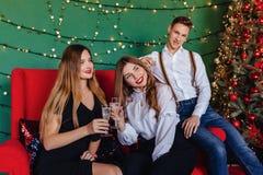 Ett ungt företag av två flickor och en grabb firar ett nytt år med exponeringsglas av champagne fotografering för bildbyråer