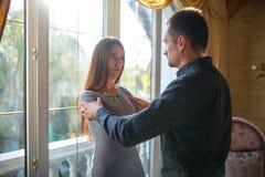 Ett ungt gift par grälar i ett modernt hus vid fönstret arkivfoto