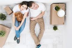 Ett ungt gift par med en röd katt, en man och en kvinna, sitter på golvet i ett ljust rum mot fotografering för bildbyråer