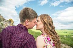 Ett ungt gift par når för en kyss på bakgrunden av en härlig natur Royaltyfria Bilder