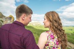 Ett ungt gift par når för en kyss på bakgrunden av en härlig natur Arkivbilder