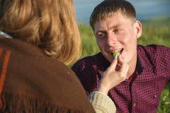Ett ungt gift par på en picknick matar sig med en injektionsspruta royaltyfri bild