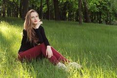 Ett ungt härligt flickasammanträde på gräs Royaltyfri Fotografi