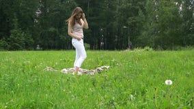 Ett ungt härligt kvinnaanseende på plädet på gräs parkerar in arkivfilmer