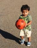 Ett ungt indiskt litet barn som spelar med bollen Arkivfoto